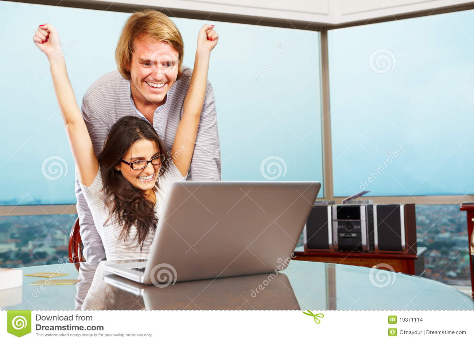 Pares felizes na frente do portátil