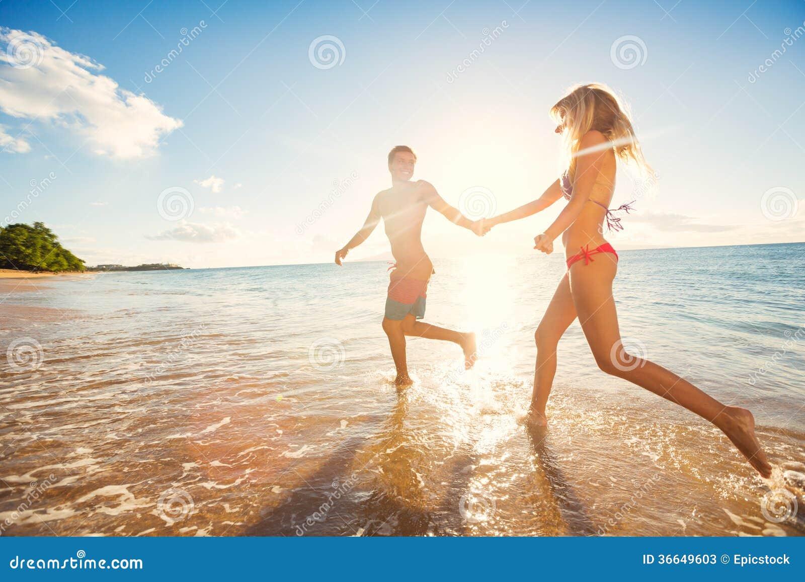 Pares felizes na praia tropical no por do sol