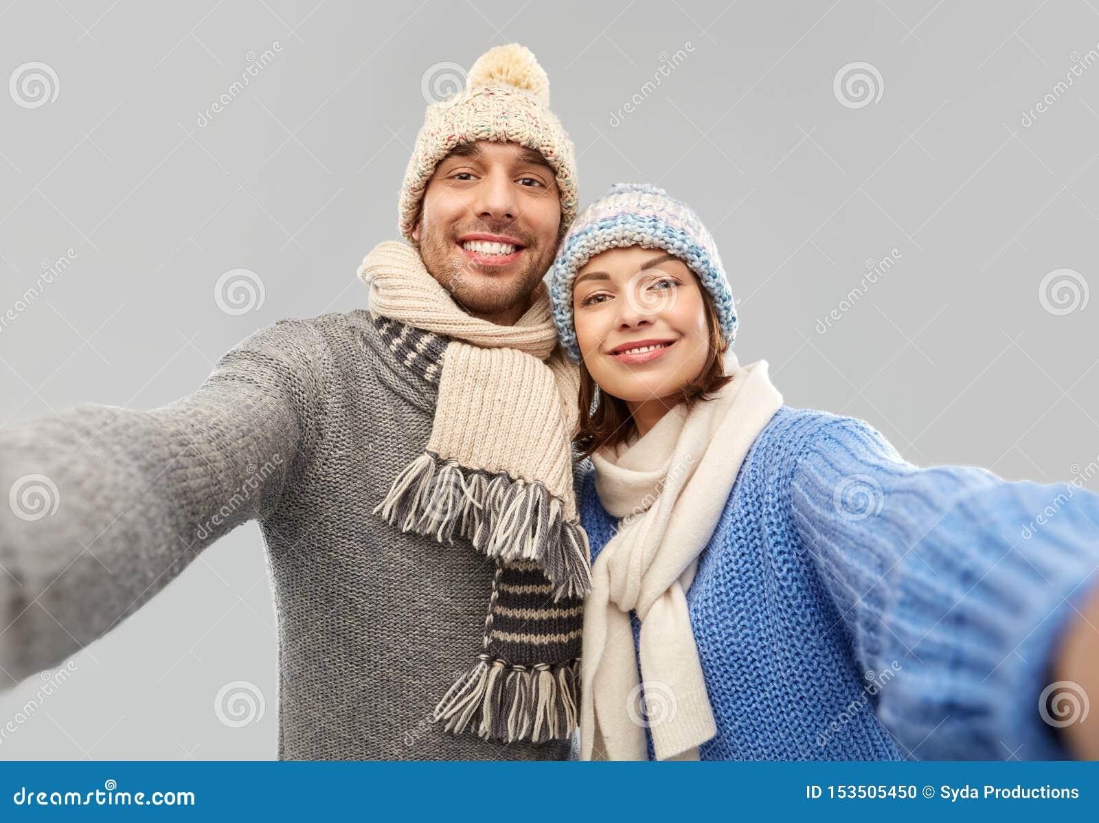 Pares felizes na roupa do inverno que toma o selfie