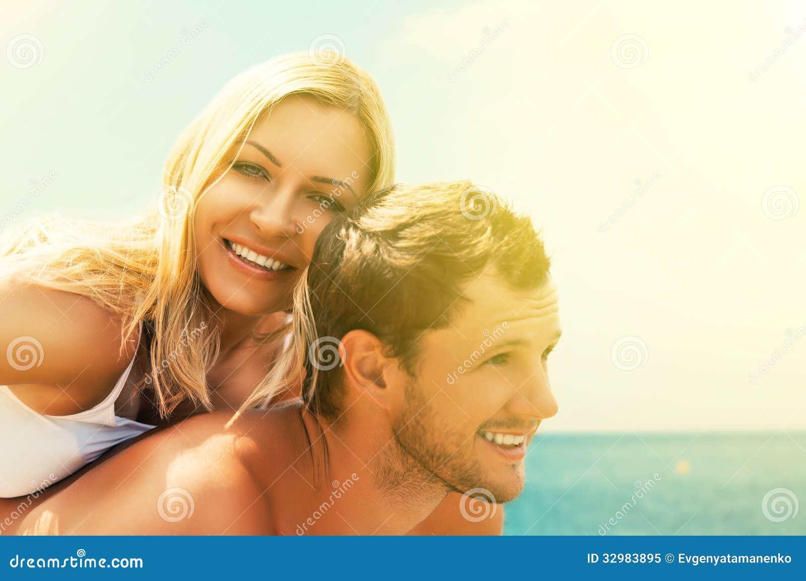 Pares felizes no amor que abraça e que ri na praia