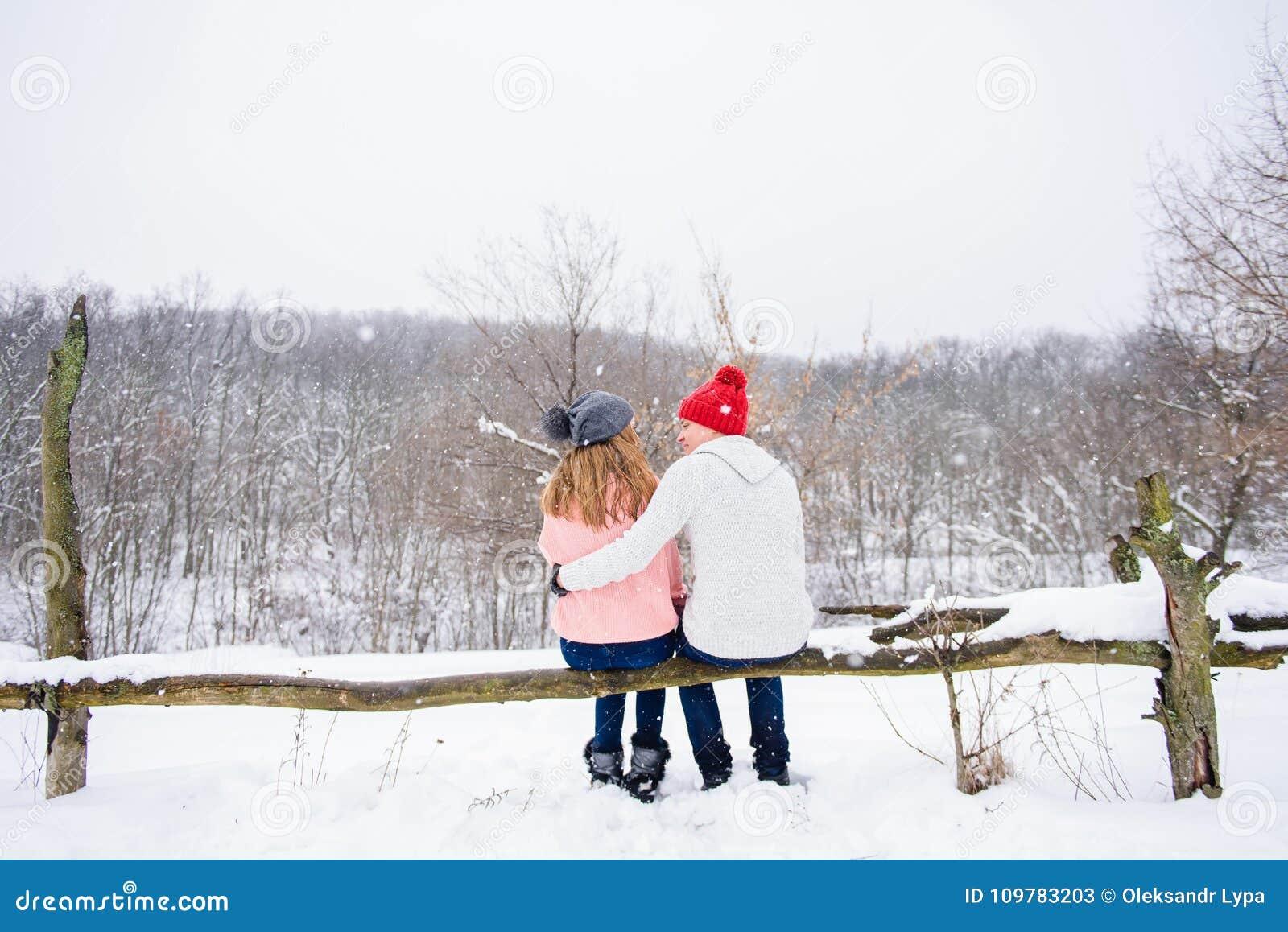 Pares felizes no fundo da neve da parte traseira