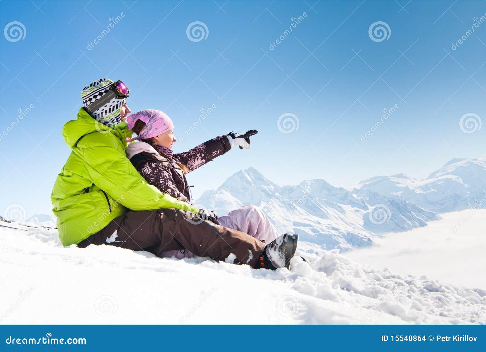 Pares felizes novos em montanhas do inverno