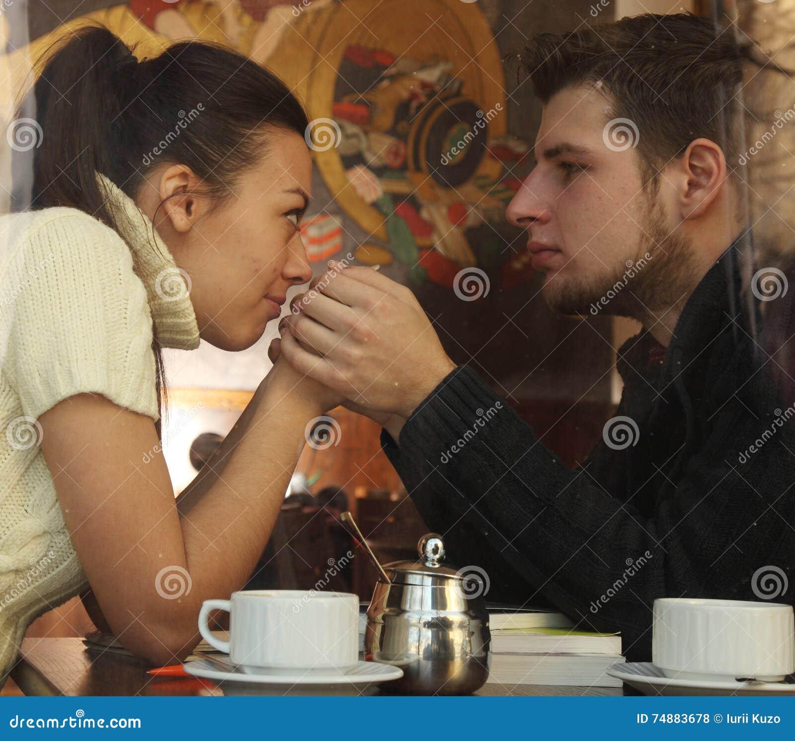Pares felizes novos no café, vista através de uma janela