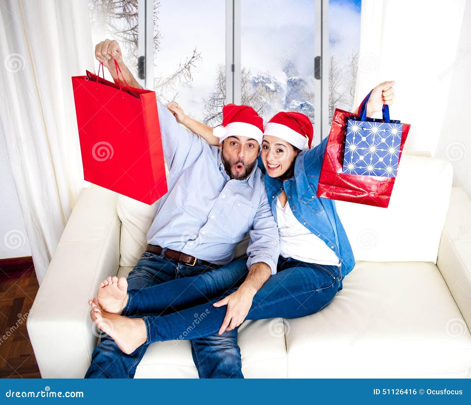 Pares felizes novos no chapéu de Santa no Natal que guarda sacos de compras com presentes