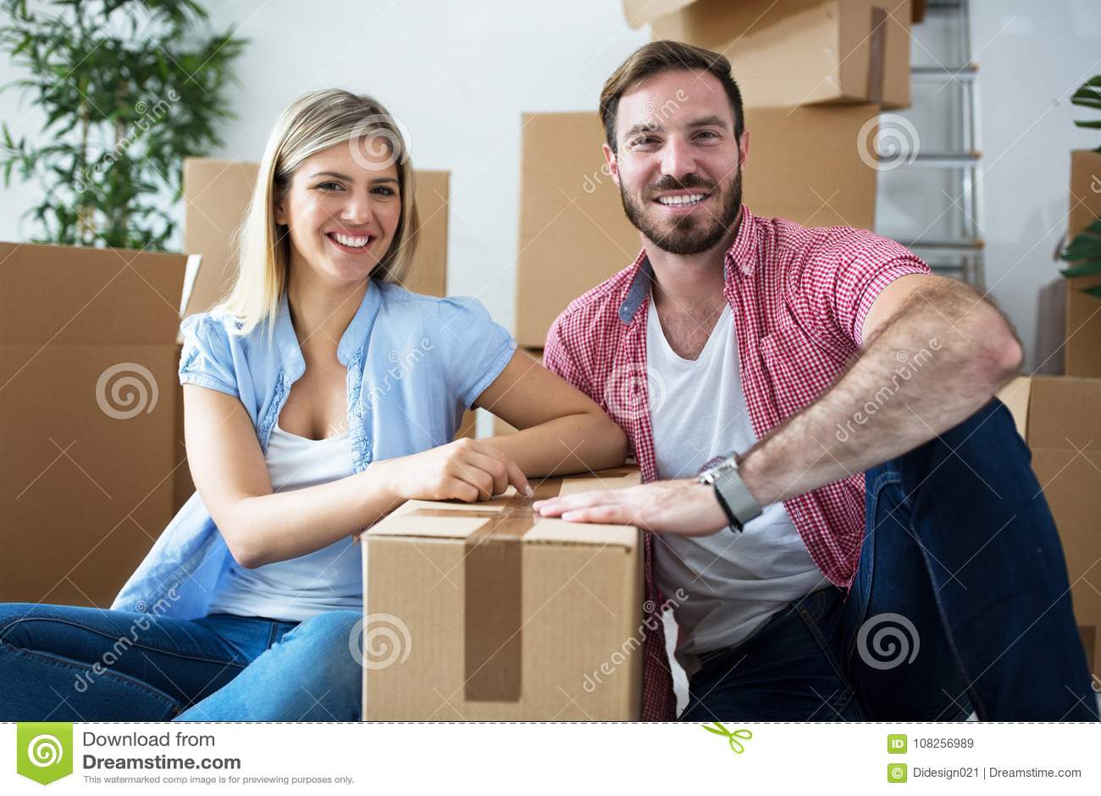 Pares felizes novos que comemoram mover-se para a casa nova
