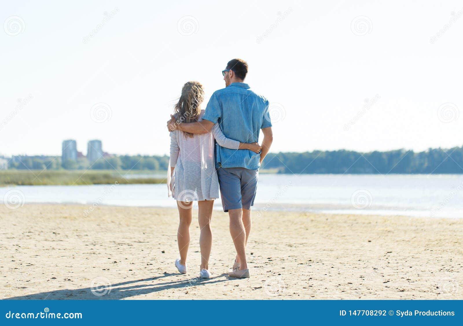 Pares felizes que abra?am na praia do ver?o