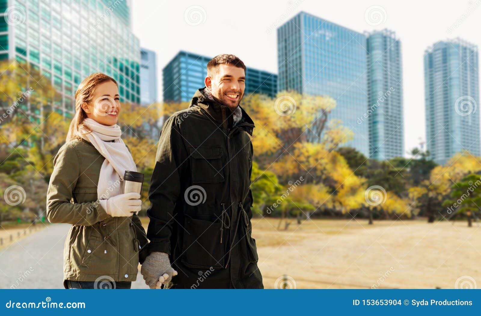 Pares felizes que andam ao longo da cidade de tokyo do outono
