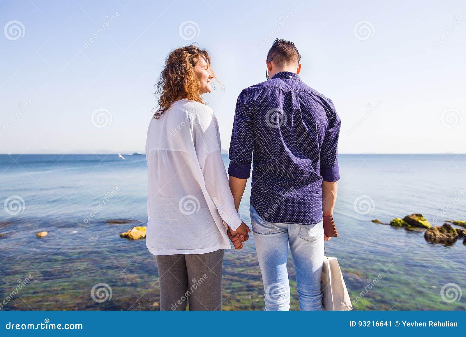 Pares felizes que estão em um cais do mar Pares à moda, guardando a mão, cabelo encaracolado, camisa branca, equipamento causal,