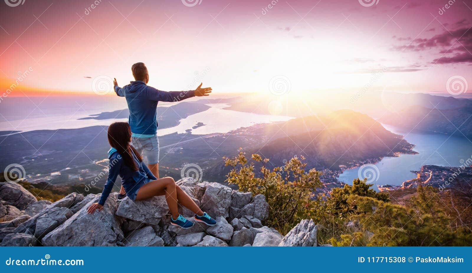 Pares felizes que olham o por do sol nas montanhas