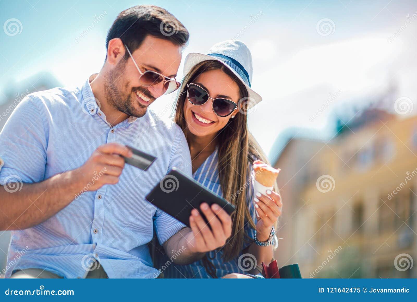 Pares felizes que pagam na linha com cartão de crédito e a tabuleta digital
