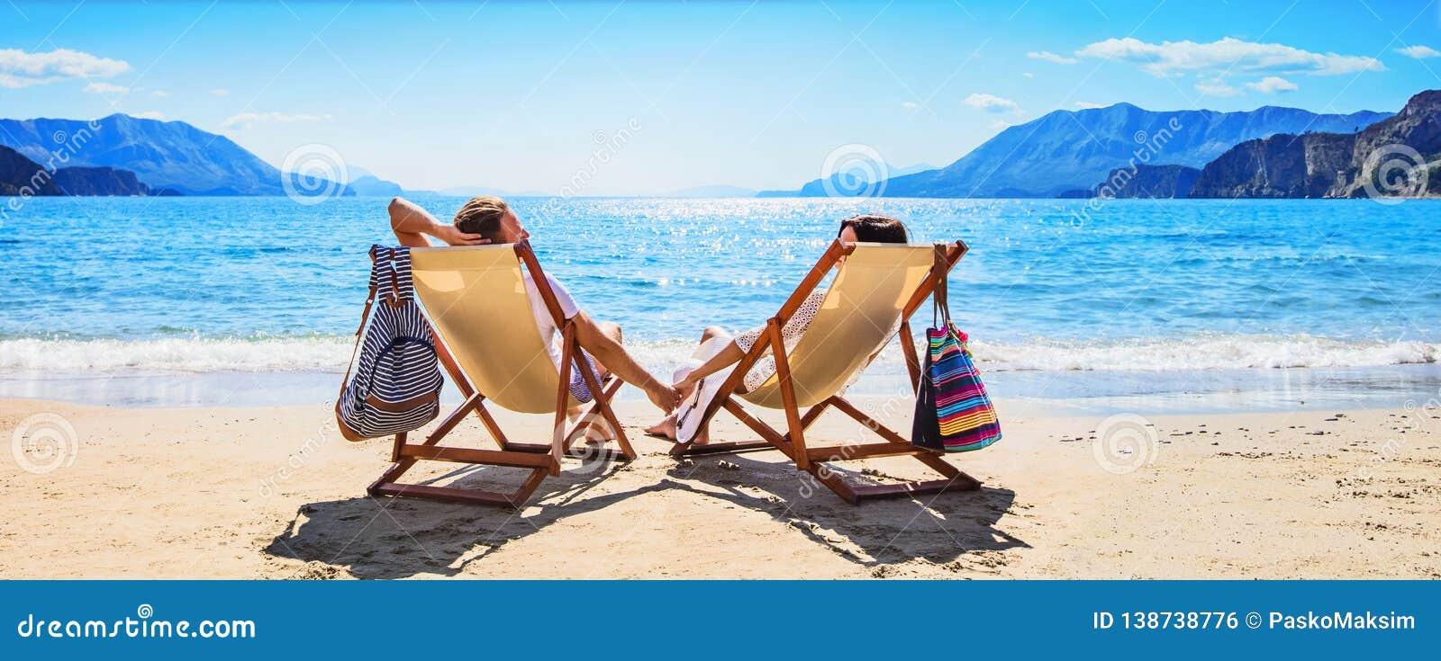 Pares felizes que relaxam na praia
