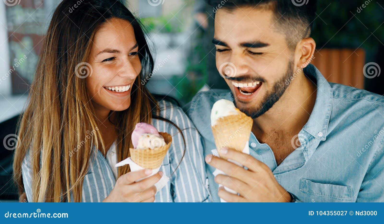 Pares felizes que têm a data e que comem o gelado