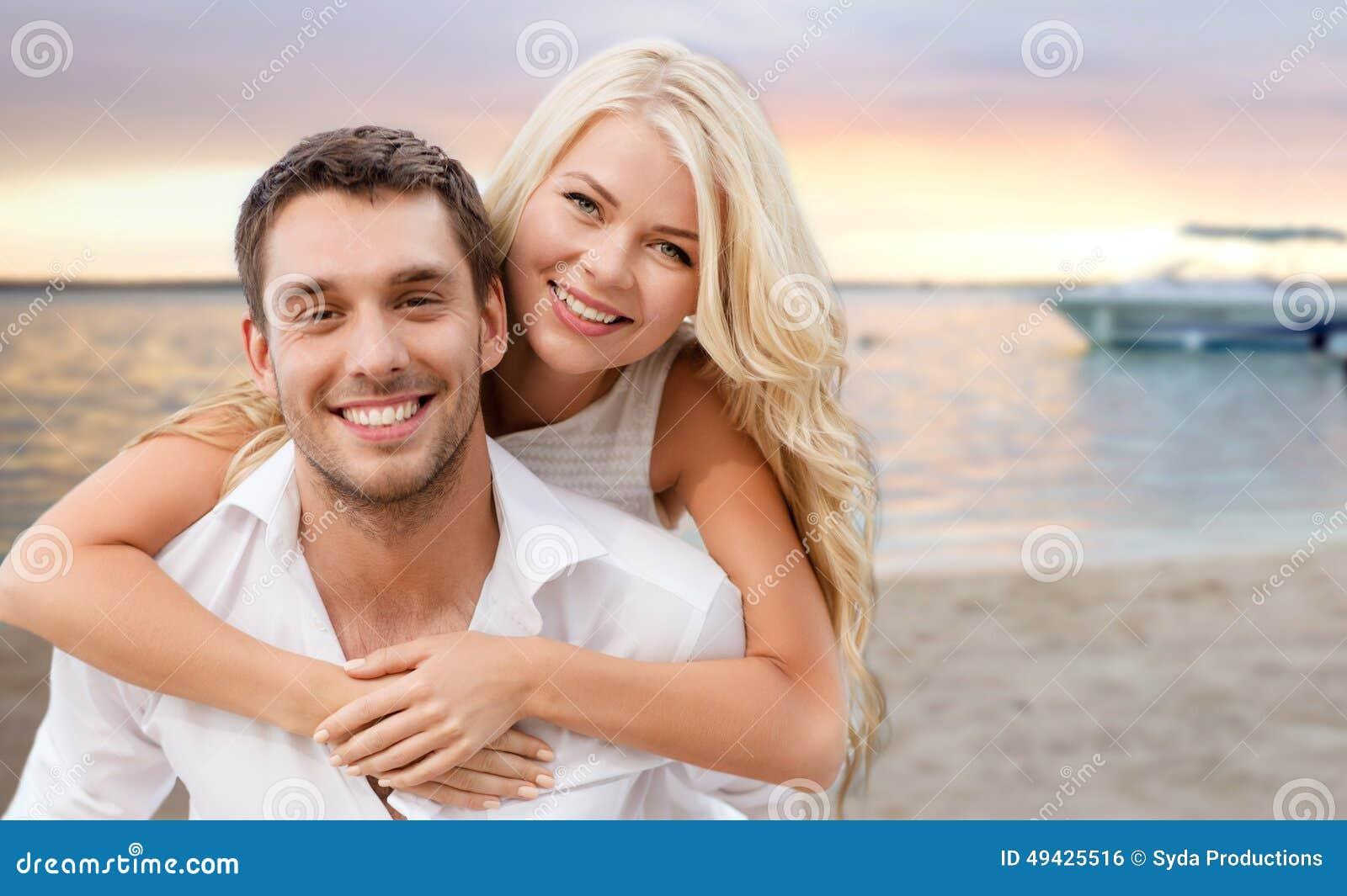 Pares felizes que têm o divertimento sobre o fundo da praia