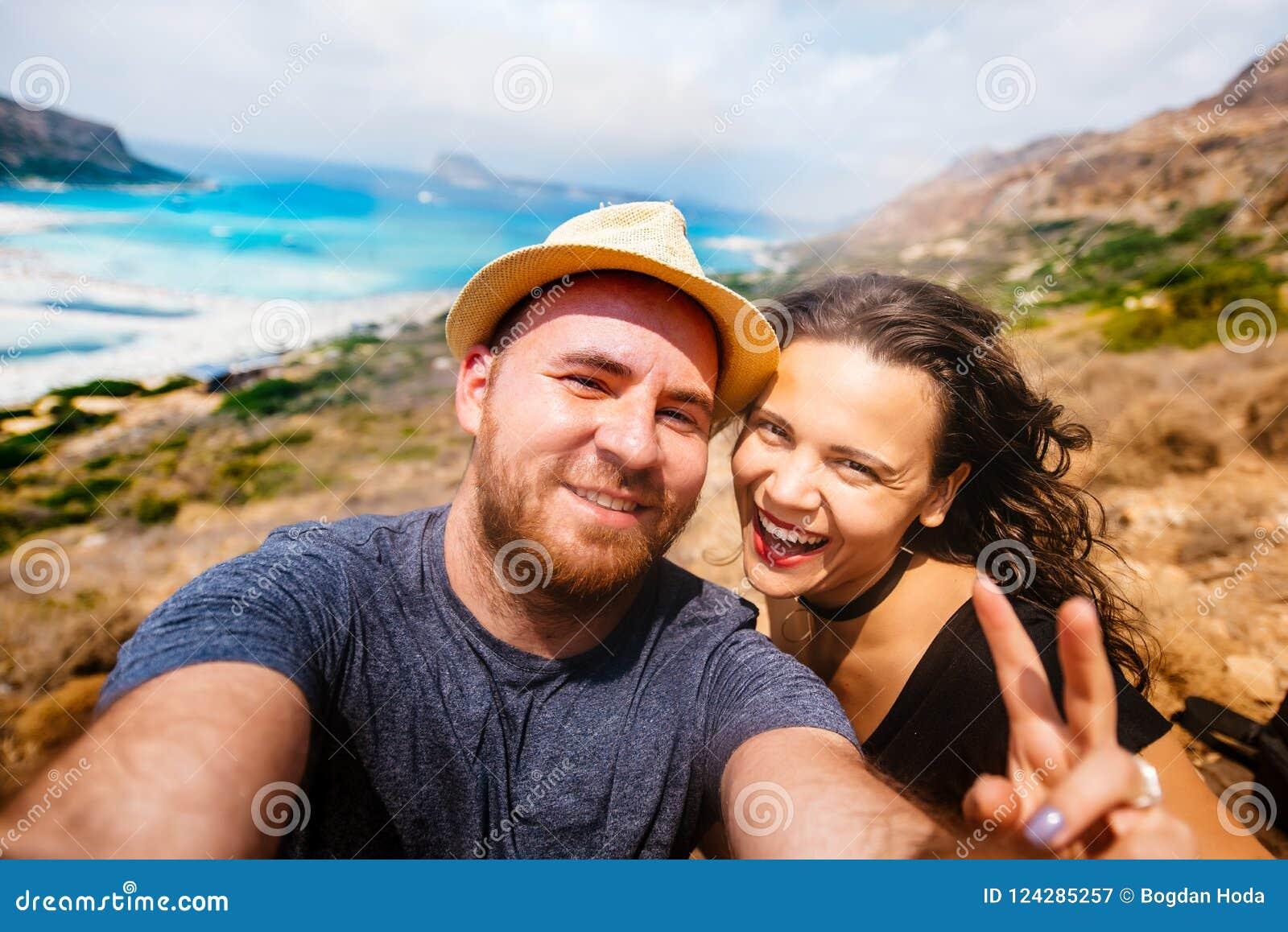 Pares felizes que tomam a foto do selfie com água da ilha e da turquesa Autorretrato dos pares nas férias