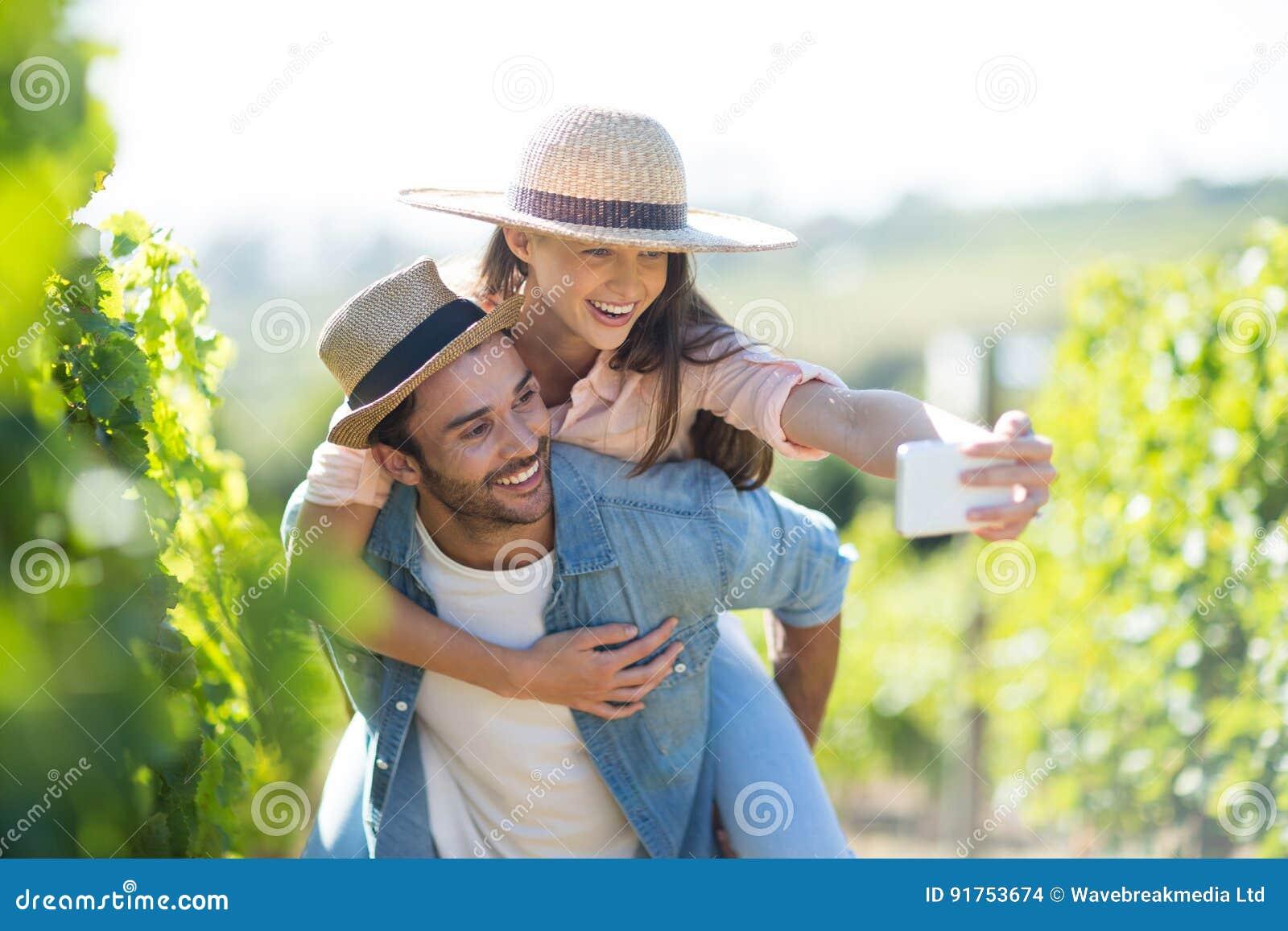 Pares felizes que tomam o selfie ao rebocar no vinhedo