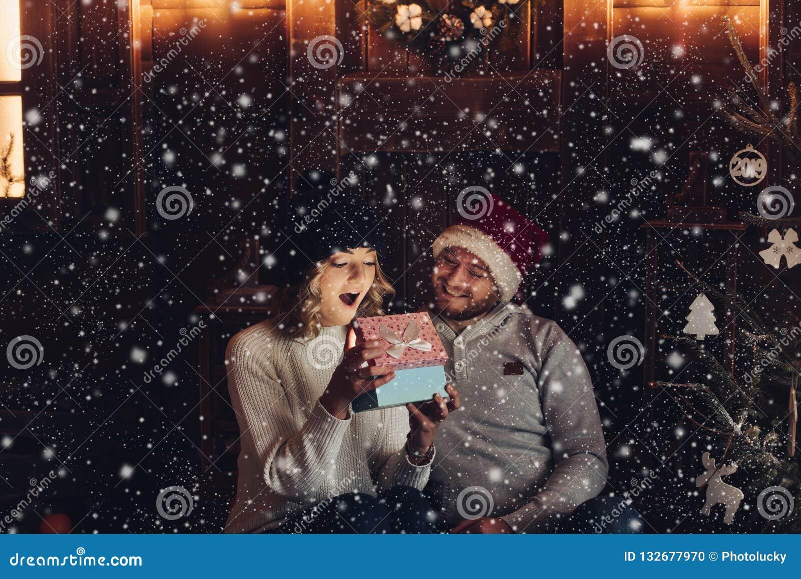 Pares felizes sob a queda de neve que olha o presente mágico