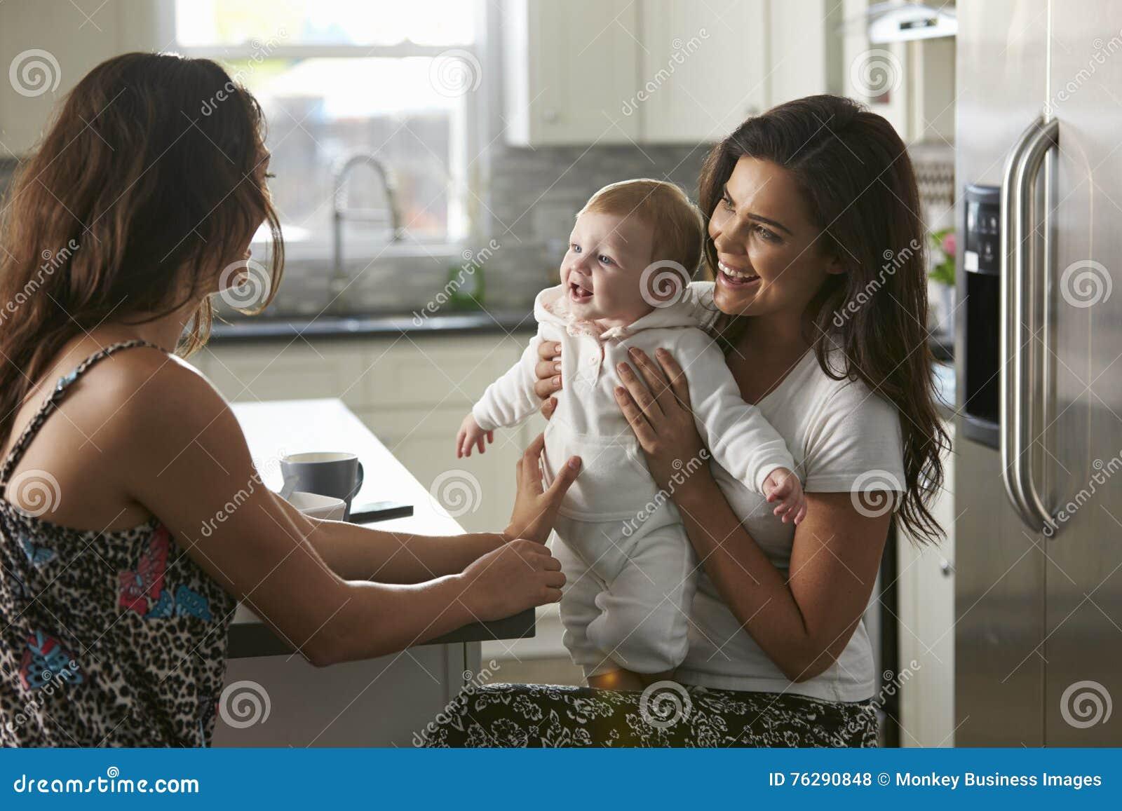 Pares femeninos que se sientan en la cocina que detiene a su bebé