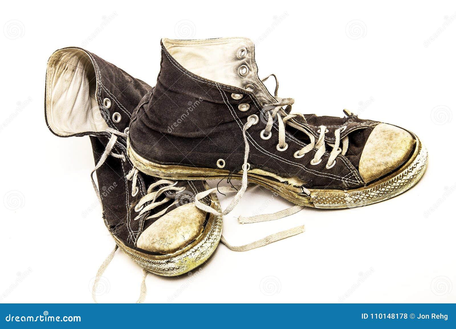 Pares gastados velhos de sapatas de tênis superiores altas preto e branco velhas no fundo branco