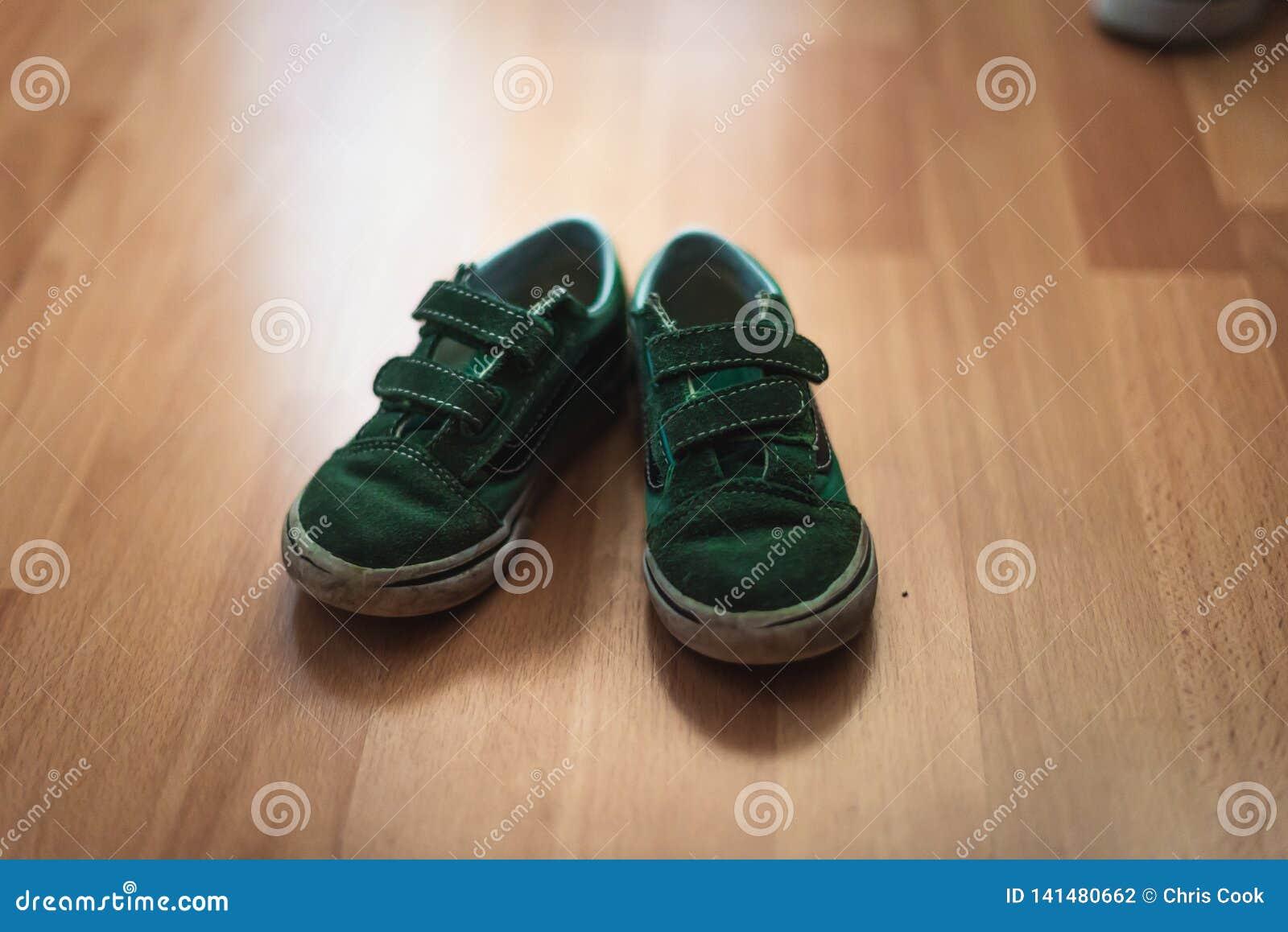 Pares gastos e enlameados de sapatas dos childs em um assoalho de madeira de uma sala de visitas