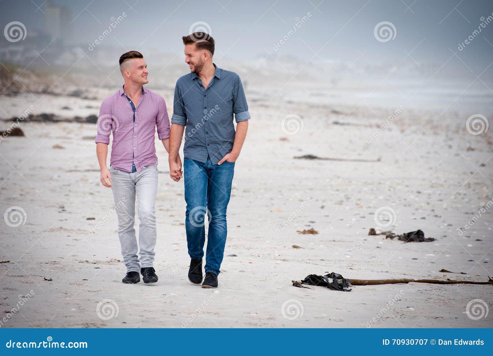 Pares gay que caminan llevando a cabo las manos