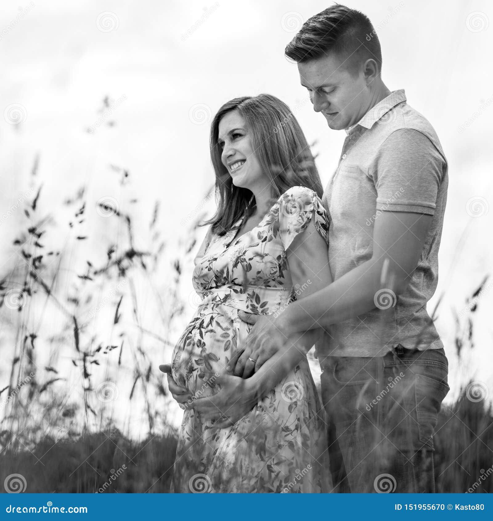 Pares grávidos felizes novos que abraçam na natureza