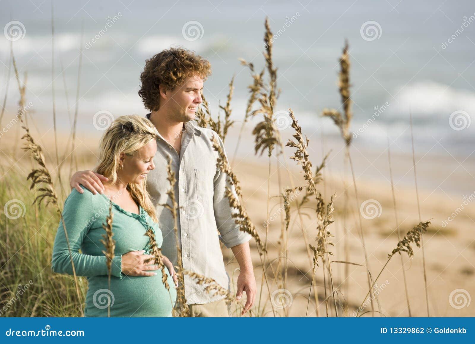 Pares grávidos felizes que estão junto na praia
