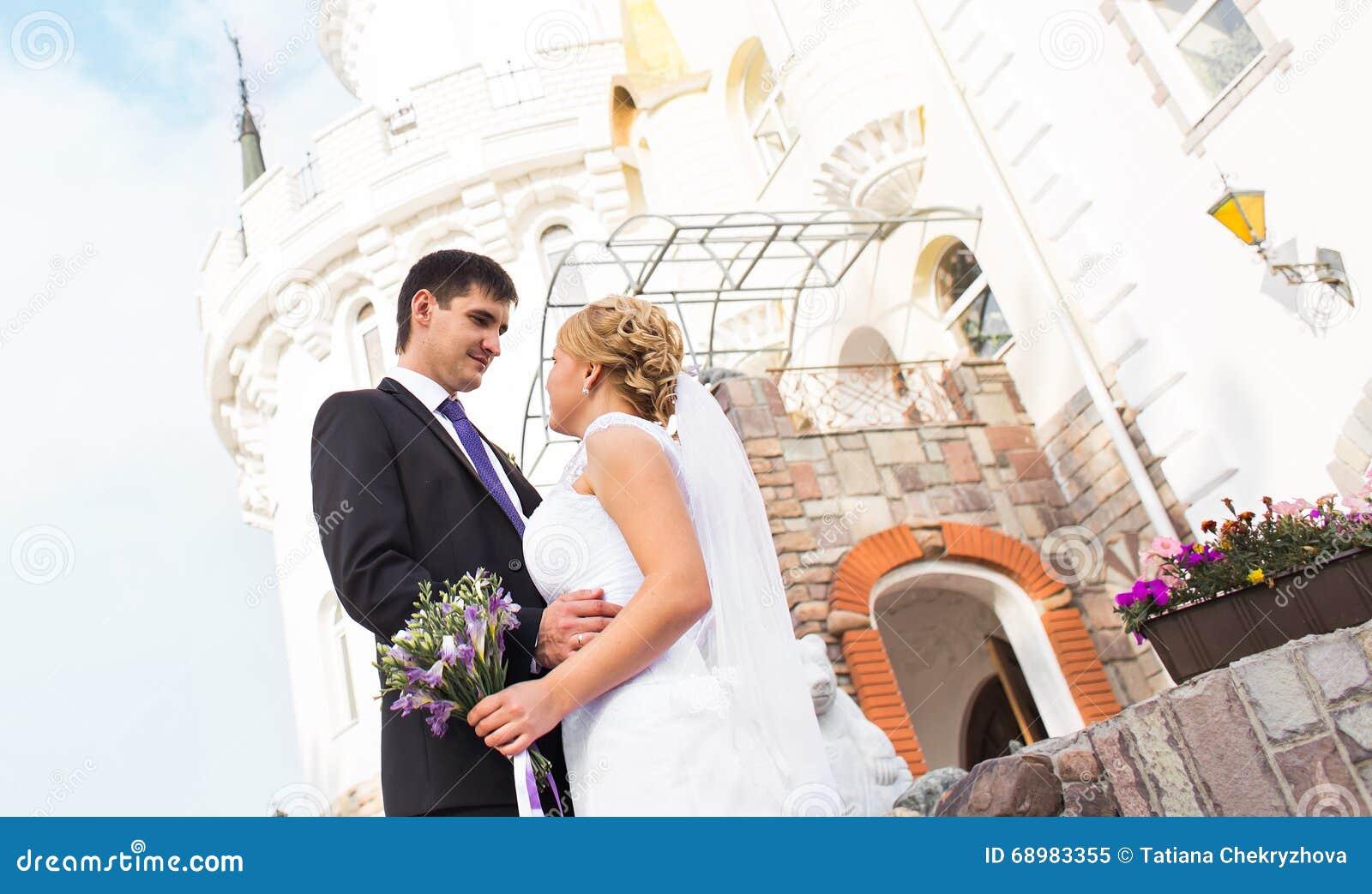 Pares hermosos de la boda al aire libre Besan y se abrazan