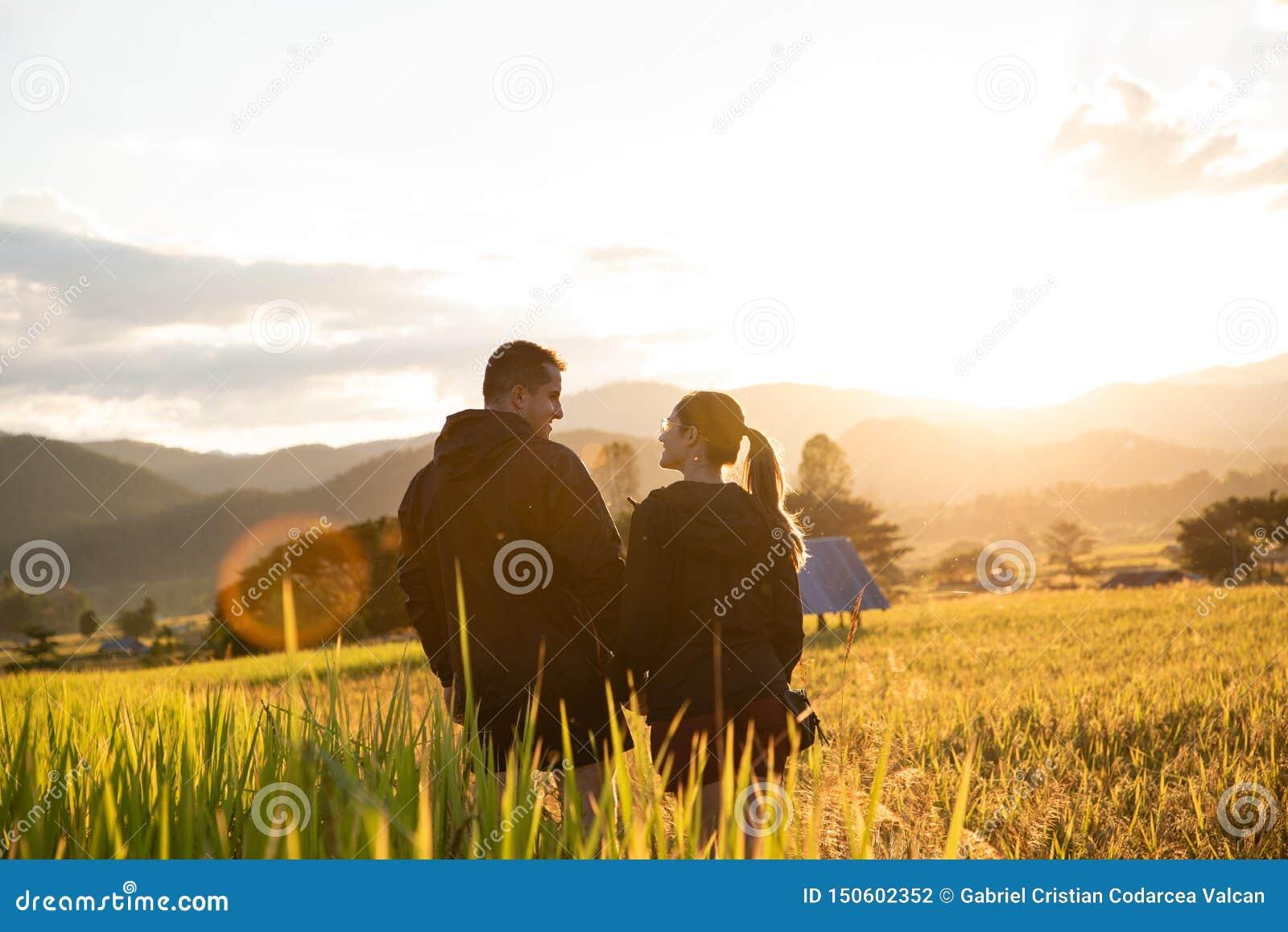 Pares hermosos del viajero en campos amarillos del arroz en Tailandia