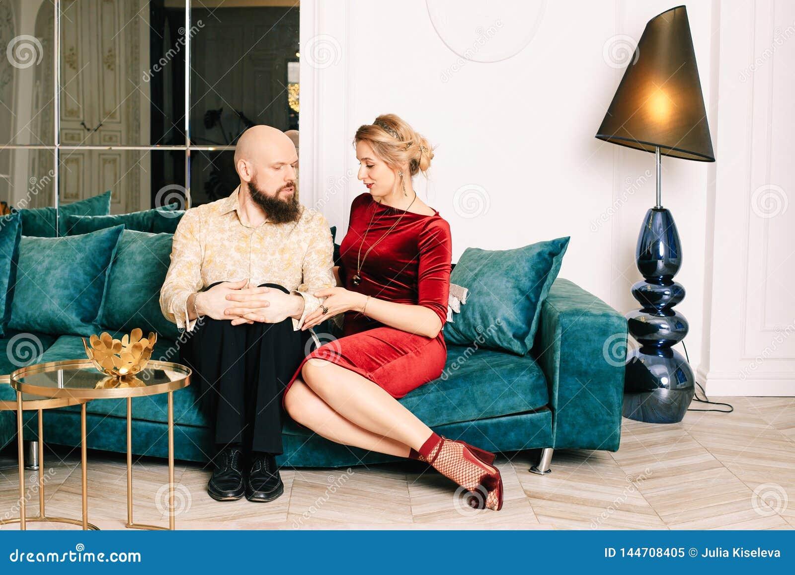 Pares hermosos en el amor que se sienta en el sof?