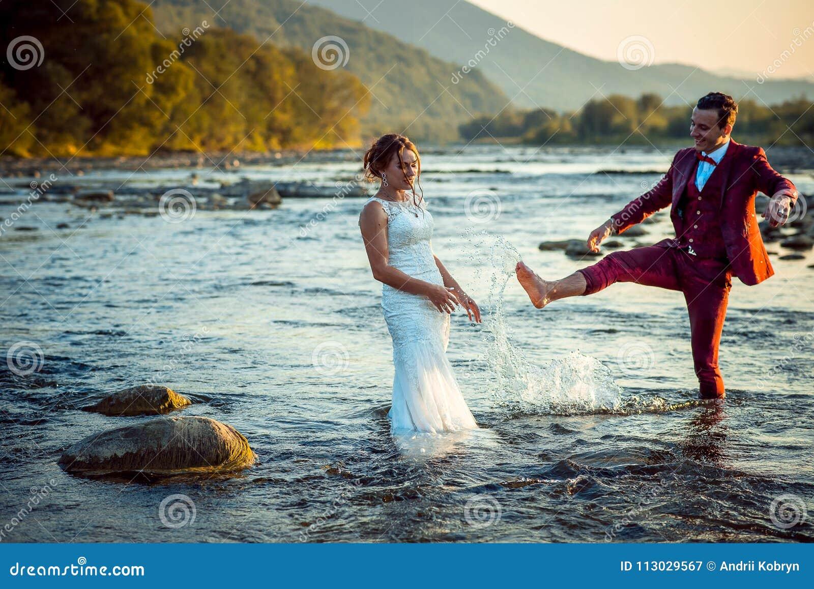 Pares hermosos felices del recién casado que se divierten en el agua mientras que el novio está salpicando el agua en su novia pr
