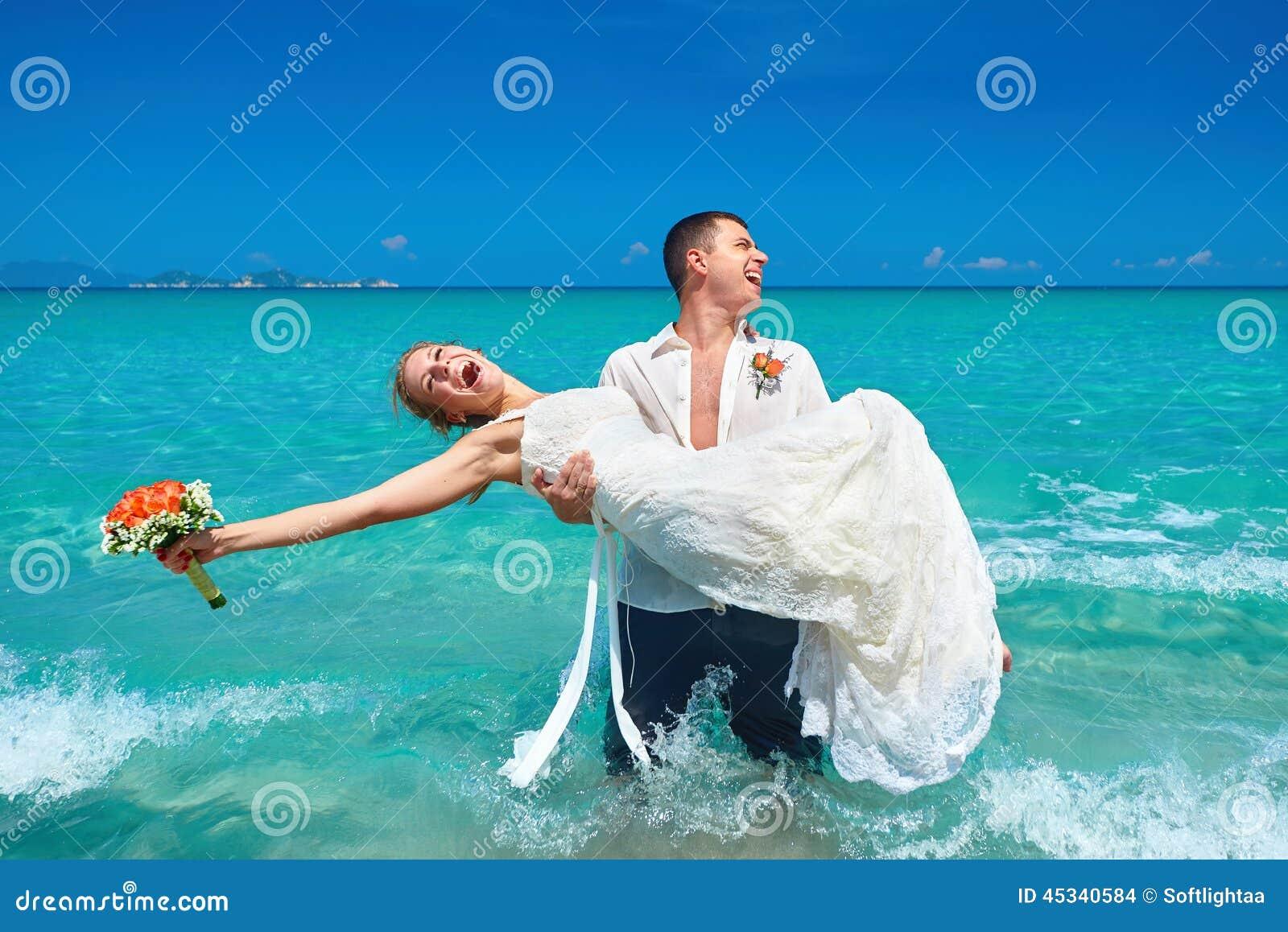 Pares hermosos felices en la playa en vestido de boda