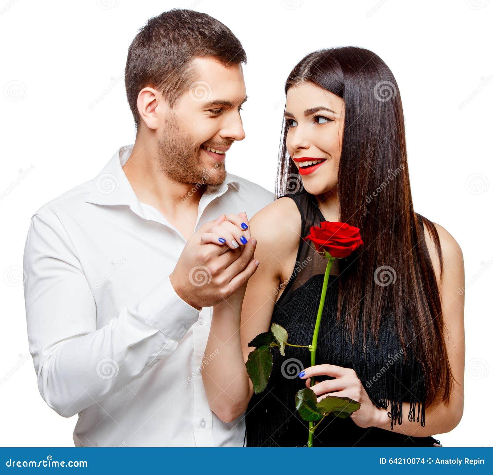 Pares hermosos jovenes con las flores aisladas en blanco