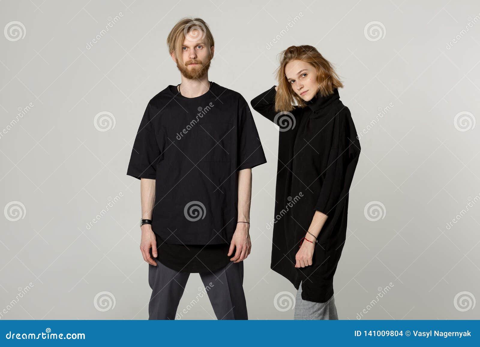 Pares hermosos jovenes en las camisetas negras que presentan en el estudio