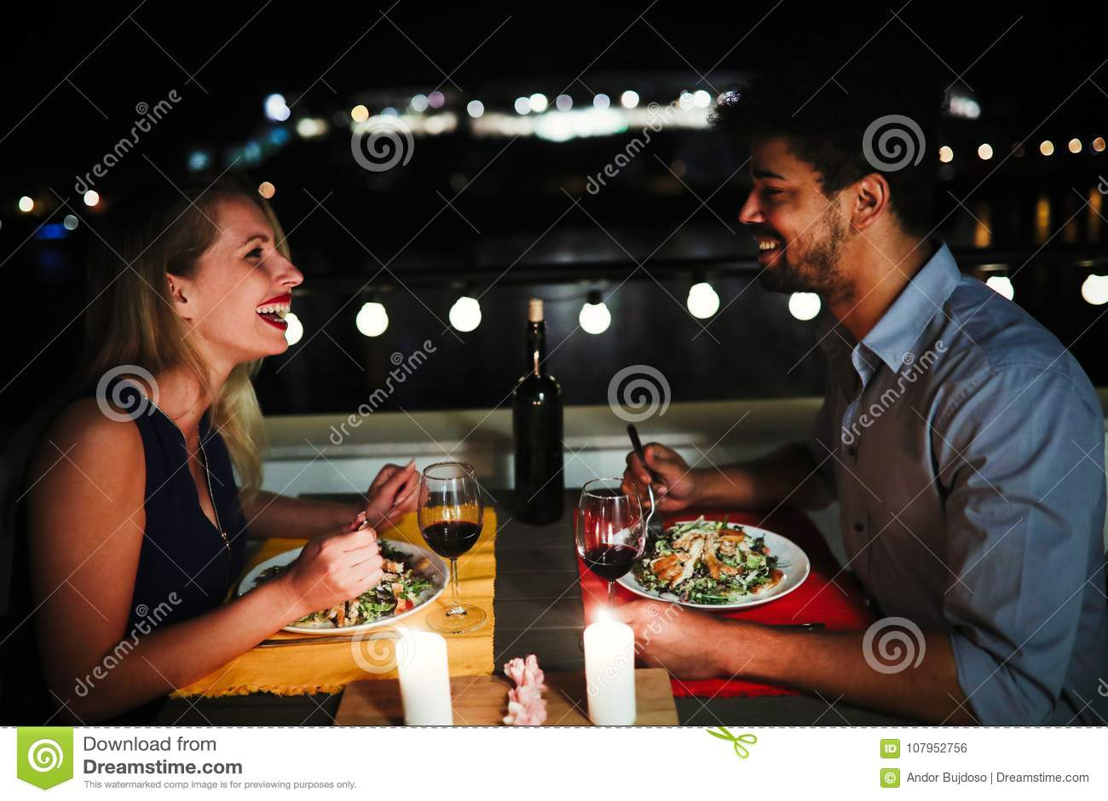 Pares hermosos jovenes que cenan romántico en tejado