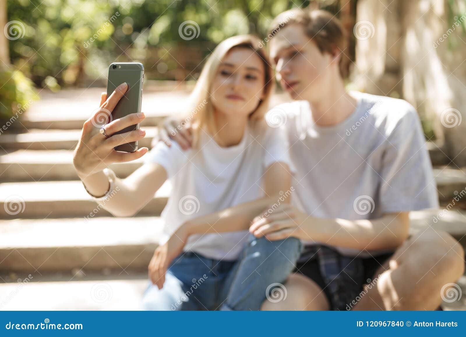 Pares hermosos jovenes que sientan y que hacen el selfie Ciérrese encima de la foto de la mano de la mujer que sostiene el teléfo