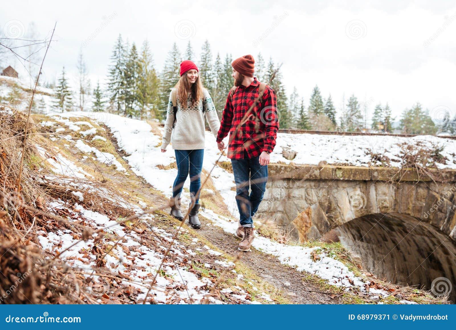 Pares hermosos que llevan a cabo las manos y que caminan al aire libre en invierno