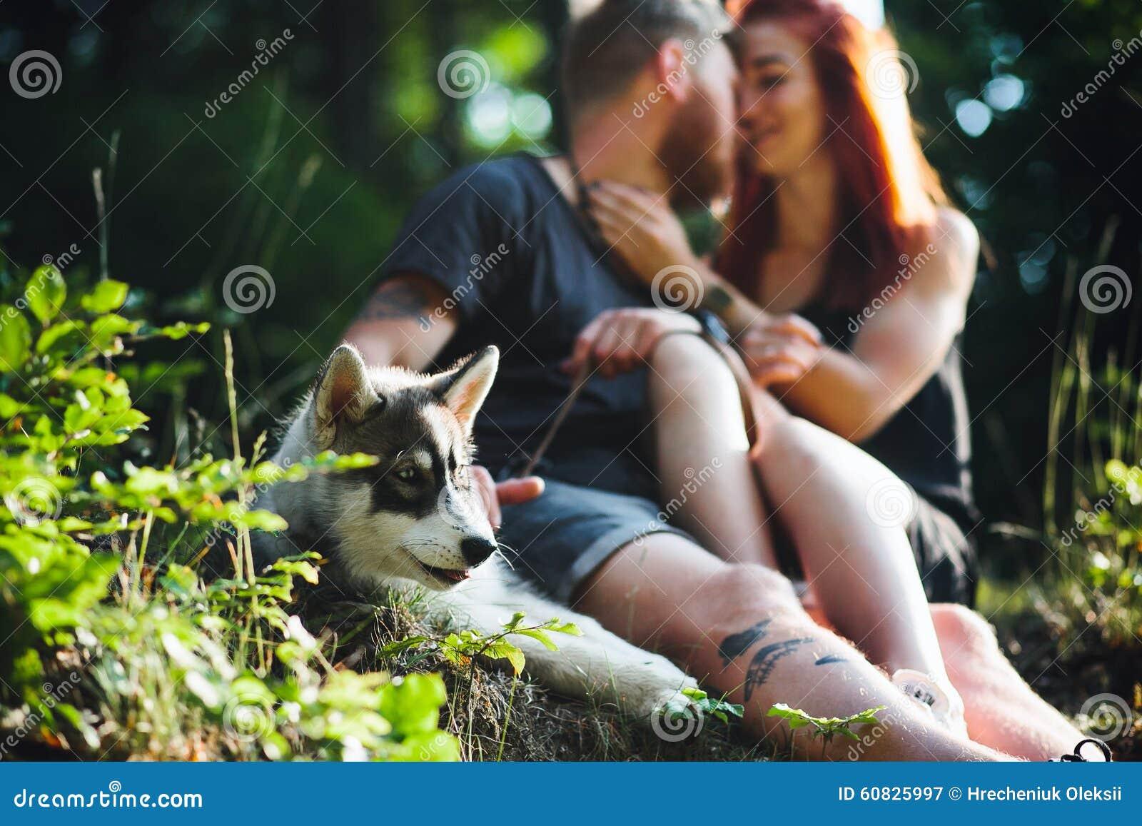 Pares hermosos que se sientan en un bosque cerca del árbol