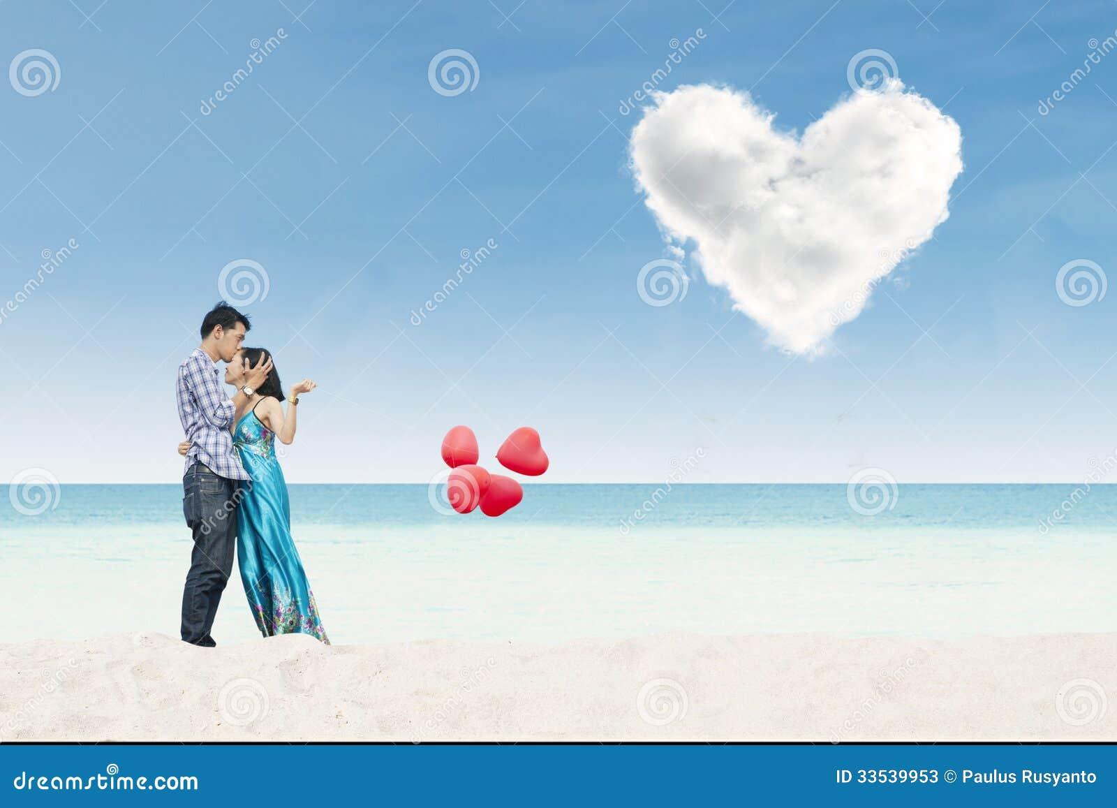 Pares hermosos que sostienen los globos del corazón en la playa