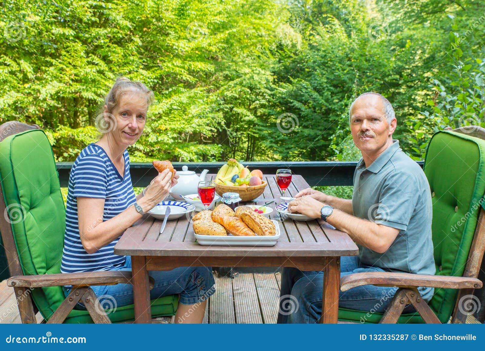 Pares holandeses que comen el almuerzo en terraza en naturaleza