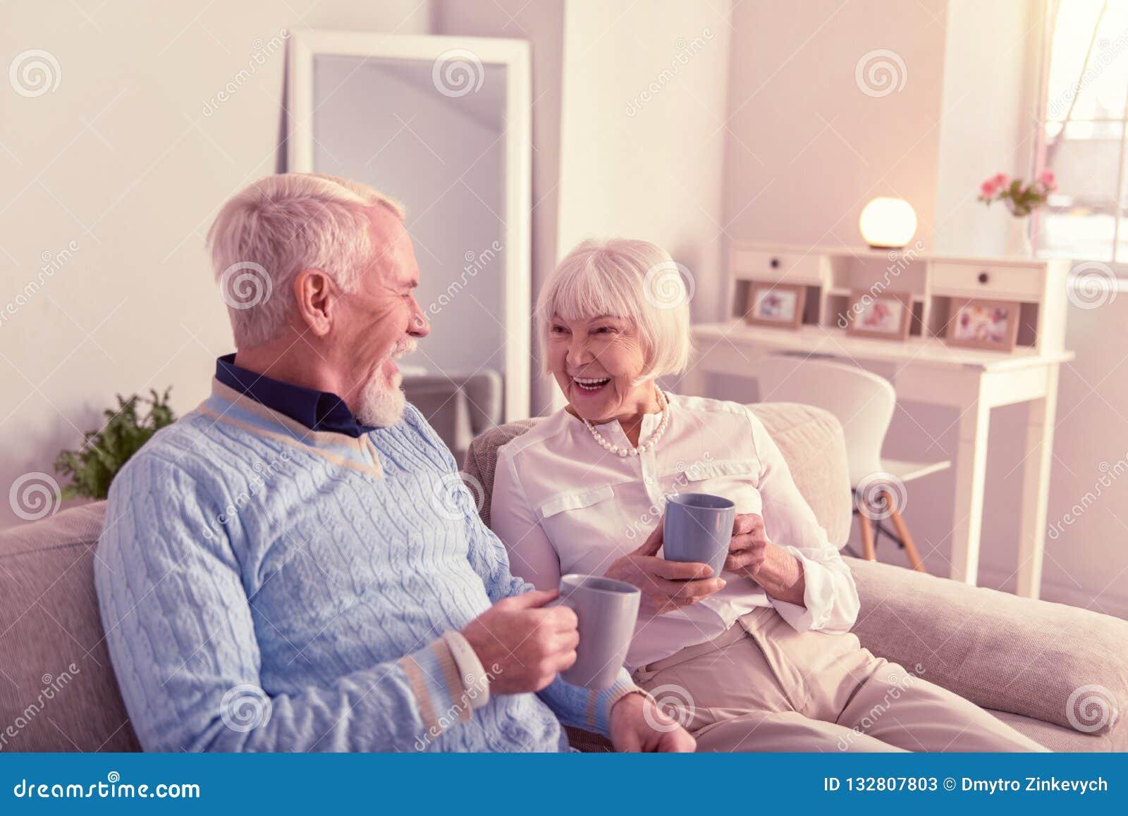 Pares idosos agradáveis que têm o grande tempo no sofá