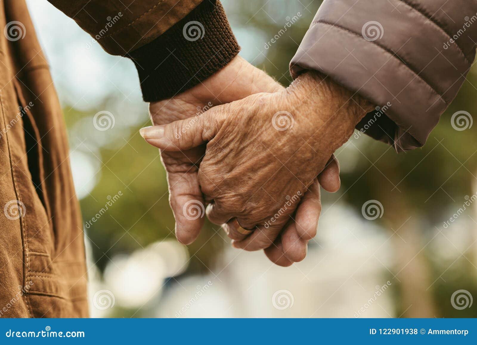 Pares idosos que guardam as mãos e o passeio