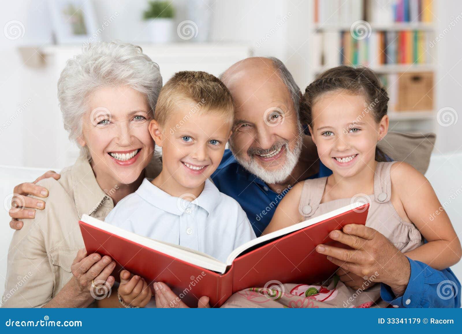 Pares idosos que leem a seus netos