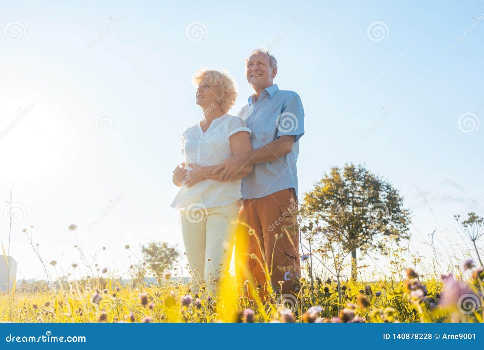 Pares idosos românticos que apreciam a saúde e a natureza em um dia ensolarado do verão