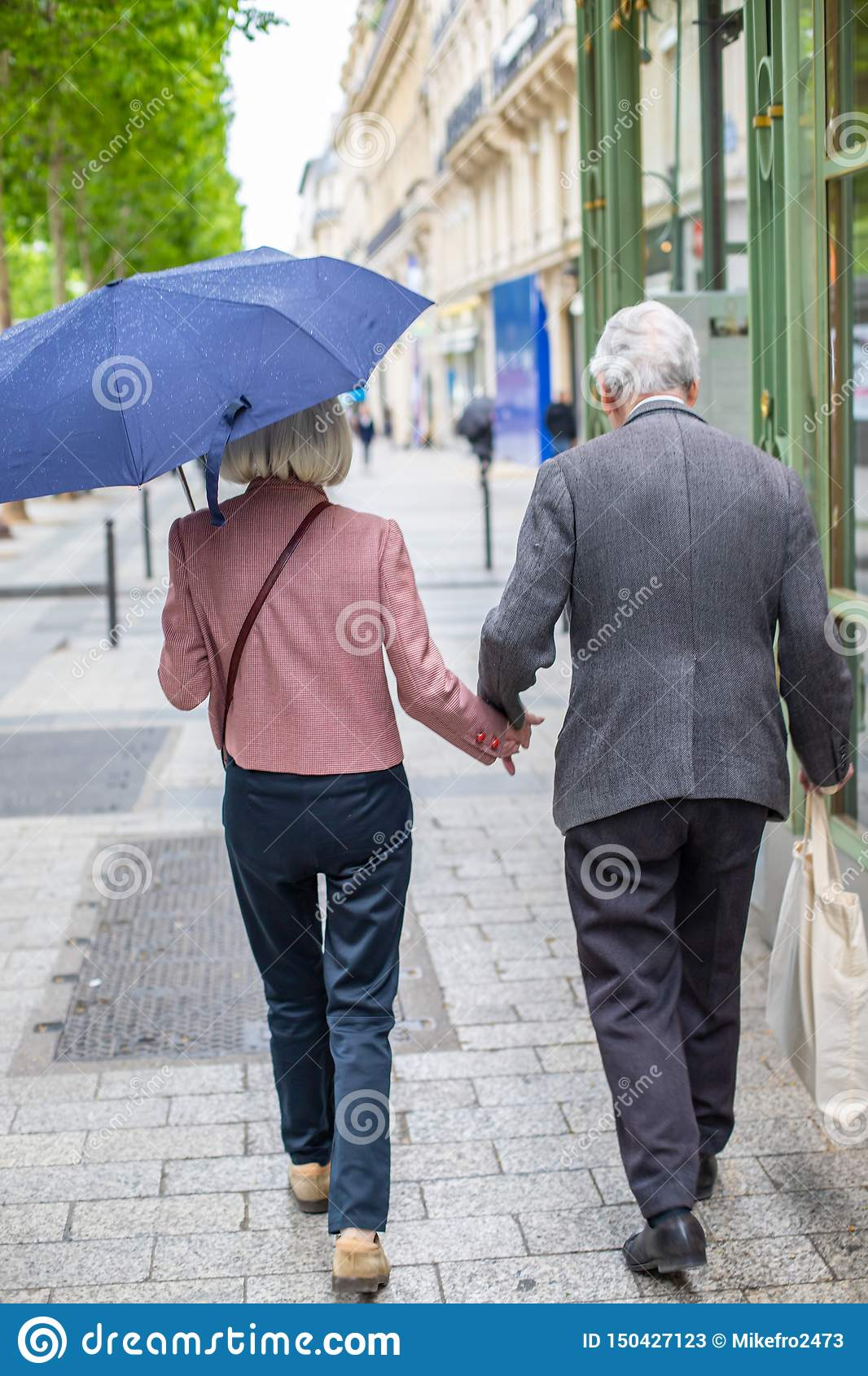 Pares idosos sob o guarda-chuva que guarda as mãos Amando-se as pessoas adultas vão abaixo da rua