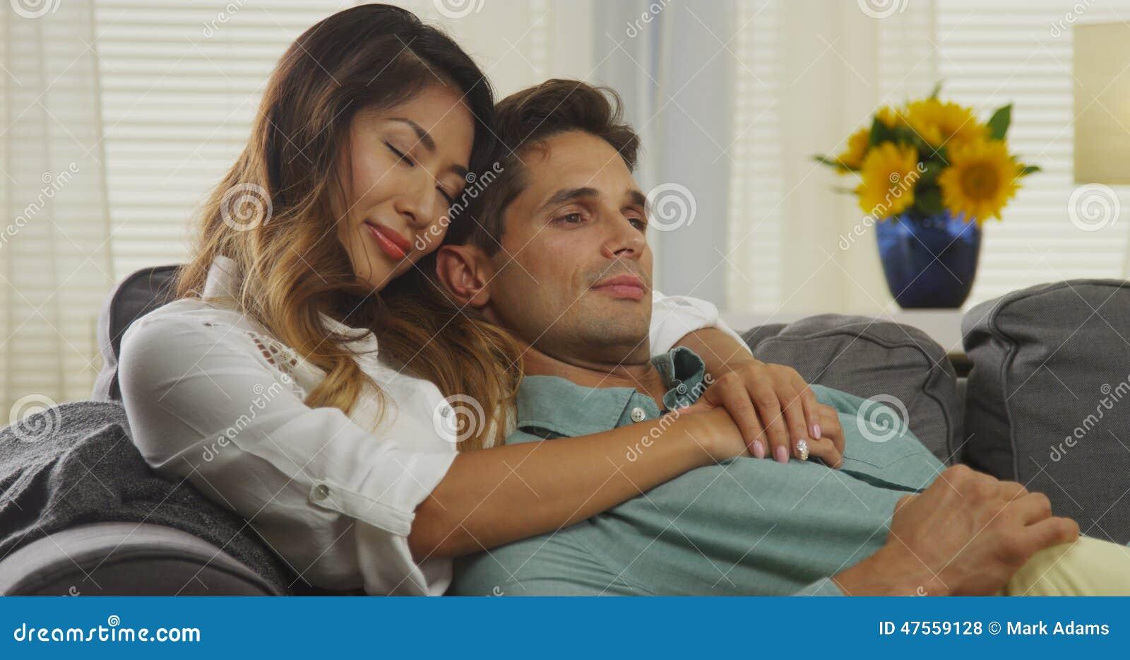 Pares interraciales que abrazan en el sofá
