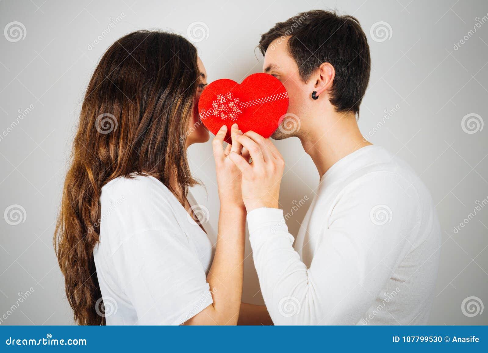 Pares jovenes alrededor a besarse detrás de una caja de regalo en forma de corazón