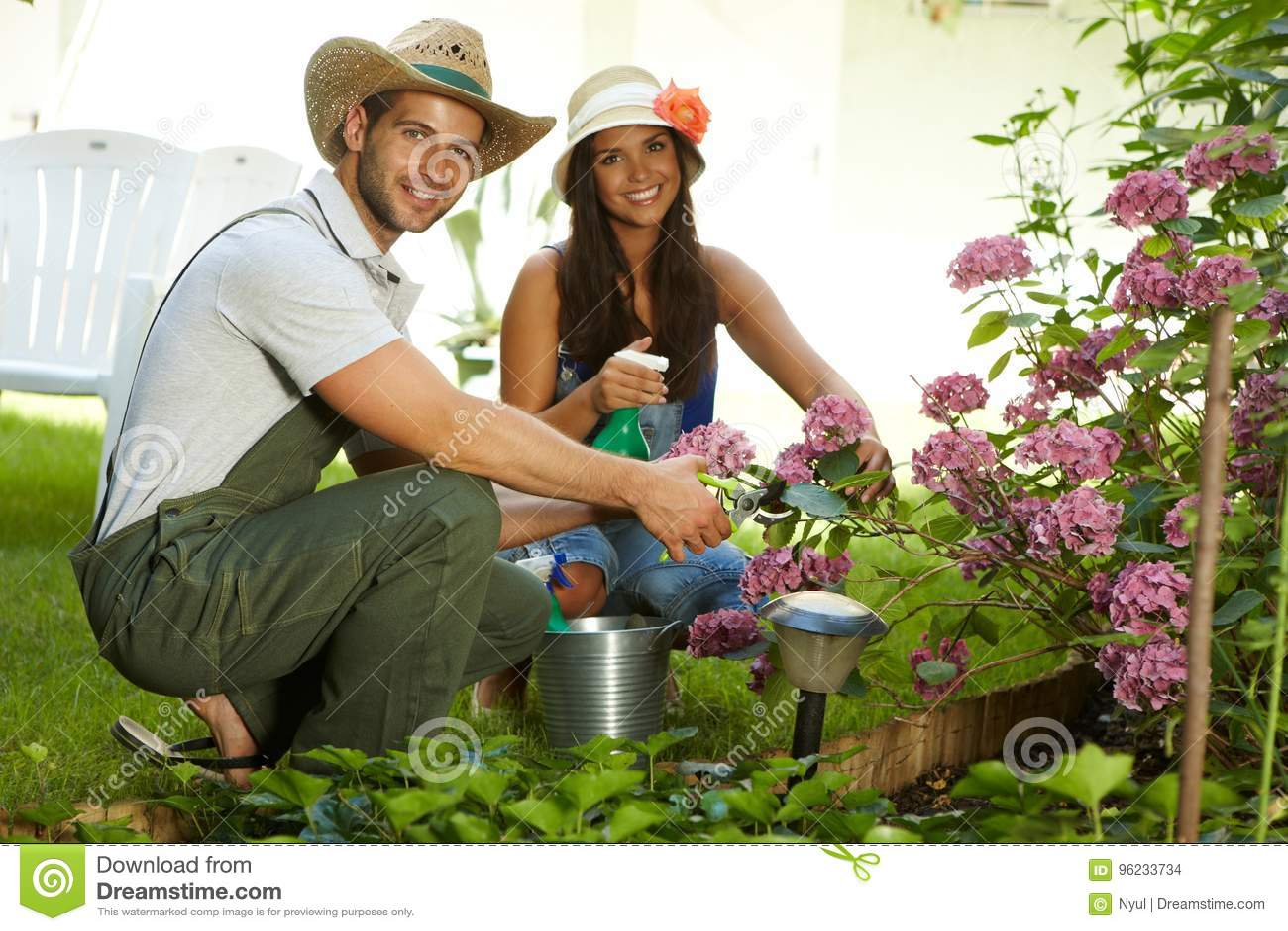 Pares jovenes atractivos que cultivan un huerto junto