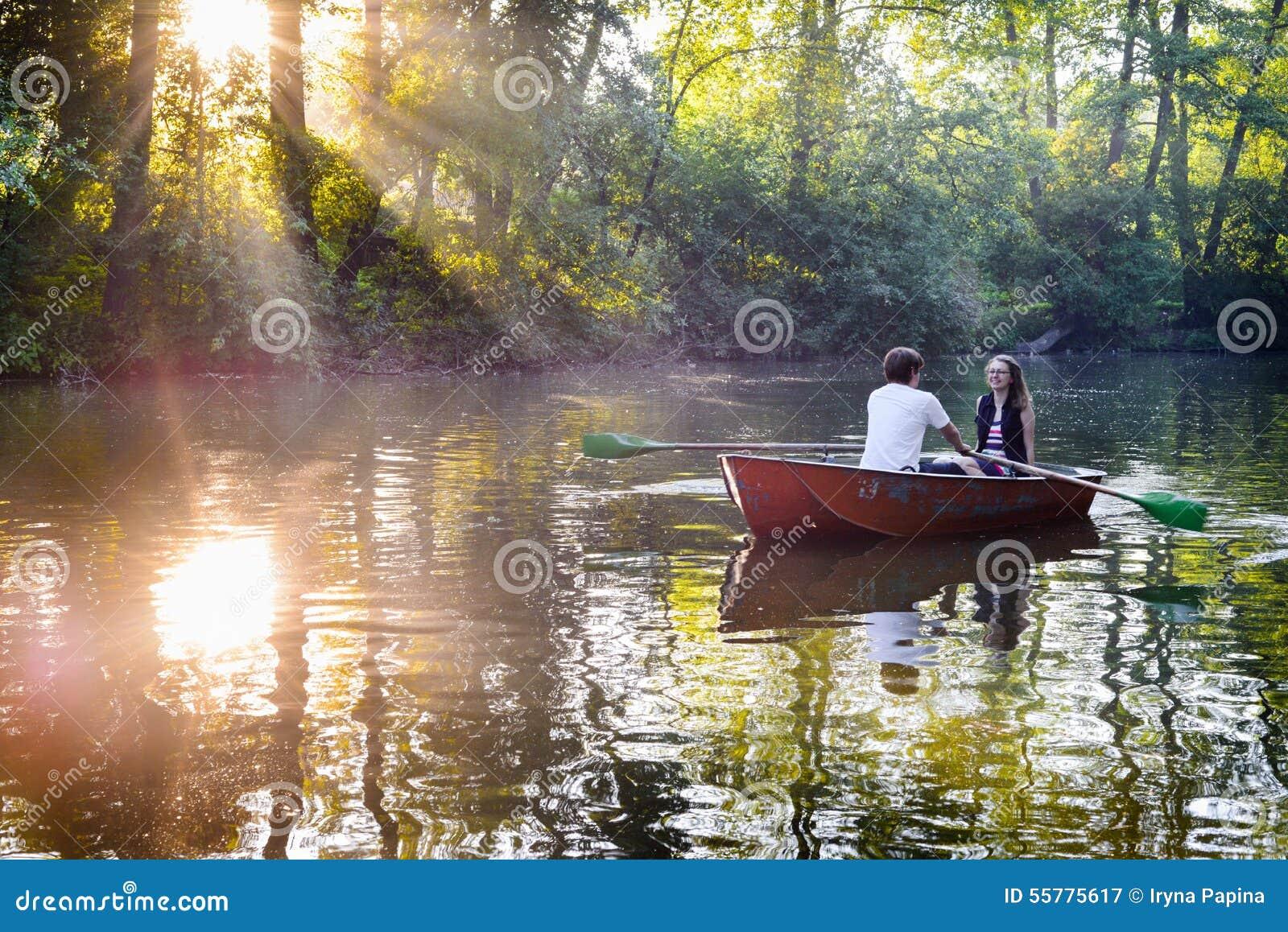 Pares jovenes cariñosos en barco en el lago que tiene tiempo romántico