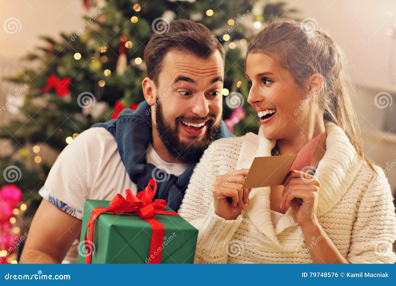 Pares jovenes con el presente sobre el árbol de navidad