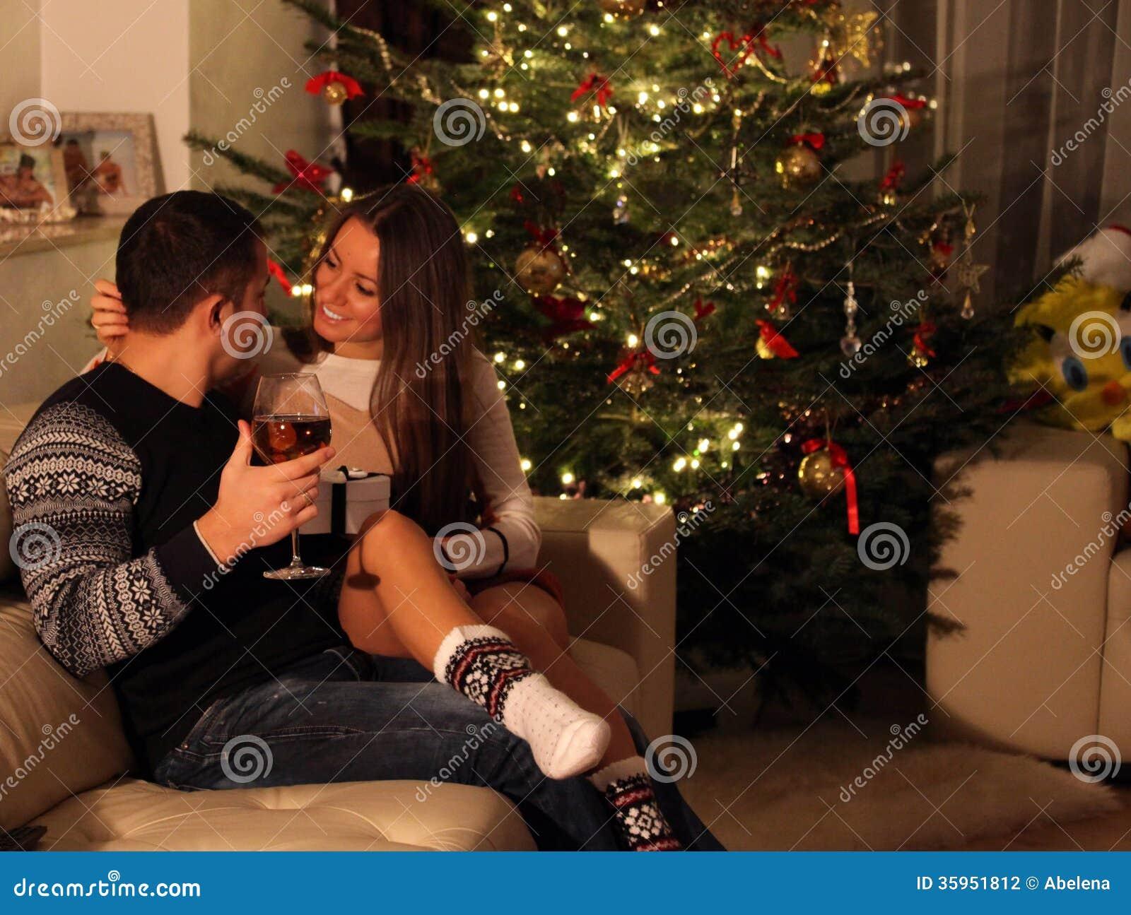 Pares jovenes con los regalos delante del árbol de navidad